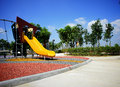Yellow slide at public playground with nice sunny day Royalty Free Stock Images
