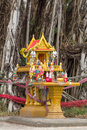 Yellow spirit house with flowers food incense candle and jar under the big tree Royalty Free Stock Image