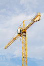 Yellow stationary hoist crane in sunlight Stock Photos