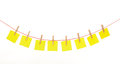 Yellow stickies hanged on red rope isolated white Royalty Free Stock Photo