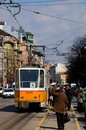 Yellow streetcar tram trolley with commuters in central sofia bulgaria march a number stops on a main road people are waiting to Royalty Free Stock Images