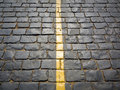 Yellow stripe on a sett paved road Royalty Free Stock Image