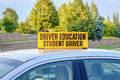 Yellow student driver sign on roof of car Royalty Free Stock Photo