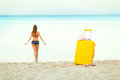 Yellow suitcase on the beach and a girl walks into the sea in th Royalty Free Stock Photo