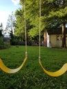 Yellow swing seats on backyard play structure Royalty Free Stock Photo