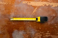 Yellow tape measure on a wooden background Stock Photo