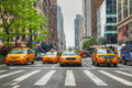 Yellow taxis at the new york city street may on may in cars serve as in nyc and are easy to spot among other Royalty Free Stock Photo