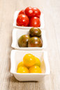 Yellow tomatoes in three bowls and vertical format Stock Photos