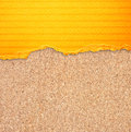 Yellow torn paper with stripes over cork board background Royalty Free Stock Photography