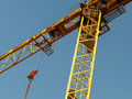 Yellow tower crane above blue sky fragment Royalty Free Stock Photo