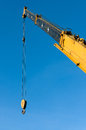 Yellow tower crane with steel hook building metal construction and blue sky Royalty Free Stock Images