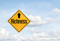 Yellow traffic sign text for richness Royalty Free Stock Photo