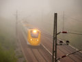 Yellow train in blurred motion in early misty morning Stock Images