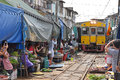 The yellow train has arrived while people are taking pictures and videos at Maeklong Railway Market. Royalty Free Stock Photo