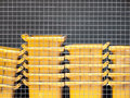 Yellow trash bin behind wire fence bins stacked up Royalty Free Stock Image