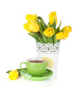 Yellow tulips and tea cup with lemon slice isolated on white background Royalty Free Stock Photo