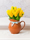 Yellow tulips in vase with blue bow on white table Royalty Free Stock Image