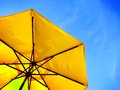 Yellow umbrella and blue sky symbolizing vacationing in summer Stock Photography