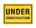 Yellow under construction sign metal plate with black text in frame attached with screw bolt isolated on white background Royalty Free Stock Photo