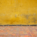 Yellow wall an old background with floor tiles Stock Photos