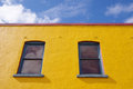Yellow wall with two windows on blue sky Royalty Free Stock Photo