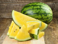 Yellow watermelon sliced on wooden background Royalty Free Stock Photo