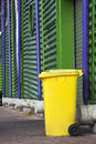 Yellow wheeled garbage can in an modern industrial area Royalty Free Stock Image
