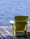 Yellow Wood Adirondack Chair on a Dock over Water Stock Photo