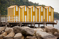 Yellow wooden cabins on beach in a row Royalty Free Stock Images