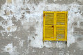 Yellow wooden window shutters on the old stone wall Royalty Free Stock Photo