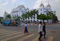 Yellow zebra crossing with a public bus and yangon city hall in the background pedestrians while is passing by majestic colonial Stock Photography