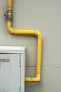 Yelow pipes and gas meter on gray wall over Royalty Free Stock Images