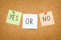 Yes or no written on red white and green post notes pinned to a board suggesting options to accept deny in a bussines look in Royalty Free Stock Photo