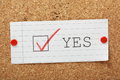 Yes tick box a for on a piece of paper pinned to a cork notice board Stock Image