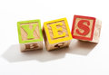 Yes in Wooden Letter Blocks on White Background Royalty Free Stock Photo