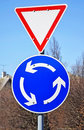 Yield traffic sign and roundabout sign on the street in the city Stock Images