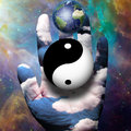 Yin yang and earth hover above hand Stock Photos