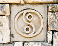 Yin and yang spiritual symbol ceramic tile in old rock wall with representing tao or taoism a chinese religion tile is one of a Royalty Free Stock Photography