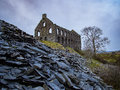 Ynys y pandy three story slate mill house in dawn light with slate spoil in the foreground near porthmadog snowdonia cymru wales Stock Image