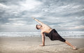 Yoga on the beach utthita parshvakonasana pose by man in black trousers near ocean in india Stock Photography