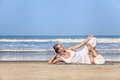 Yoga on the beach woman doing in white costume near ocean in goa india Royalty Free Stock Image