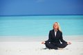 Yoga business woman lotus pose beach Stock Image