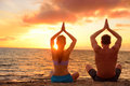 Yoga couple relaxing doing meditation on beach silhouettes of men and women people practicing pose sitting at a in the Royalty Free Stock Images