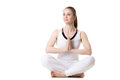 Yoga easy pose portrait of young beautiful girl in white sportswear doing practice sitting cross legged in sukhasana with hands in Stock Images