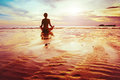 Yoga and enlightenment silhouette of woman practicing on the beach Royalty Free Stock Photos