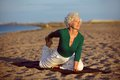 Yoga exercise on the beach senior woman in stretching position by sea at morning elderly woman doing Royalty Free Stock Photos