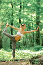 Yoga king of the dance pose by woman on green grass in the park Royalty Free Stock Photo