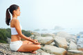 Yoga lifestyle woman beach doing pose at the ocean for zen health and peaceful Stock Image