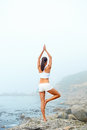 Yoga lifestyle woman beach doing pose at the ocean for zen health and peaceful Stock Photos