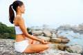 Yoga lifestyle woman beach doing pose at the ocean for zen health and peaceful Royalty Free Stock Photo